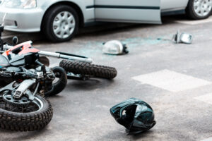 motorcycle on its side with helmet next to it after being hit by car.