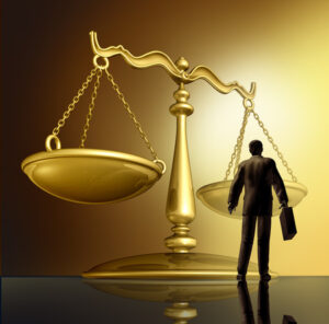 Scales of justice with silhouette of attorney under them.
